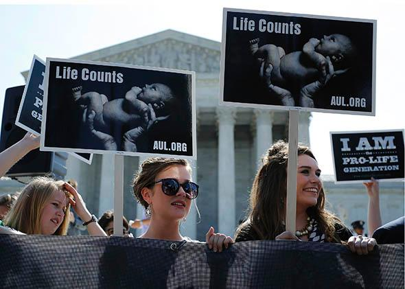 Anti-abortion demonstrators wait for the U.S. Supreme Court ruling in the Hobby Lobby.