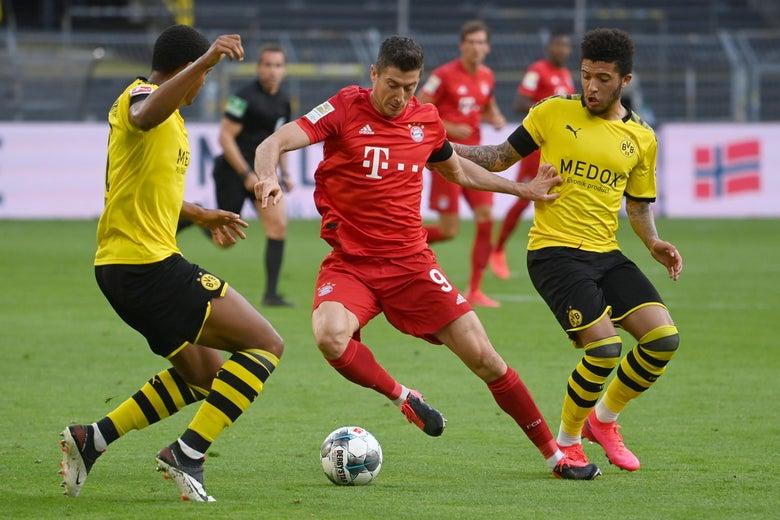 Robert Lewandowski of Bayern Munich is challenged by Jadon Sancho and Manuel Akanji of Borussia Dortmund