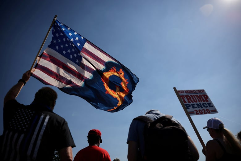 A man in a thin blue line t-shirt holds an American flag that is half emblazoned with a flaming Q beside another person holding a Trump-Pence 2020 sign, all seen from behind.