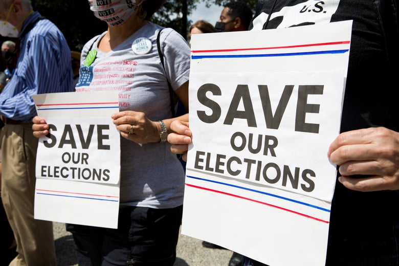 """Two people hold up signs that say """"Save Our Elections."""""""