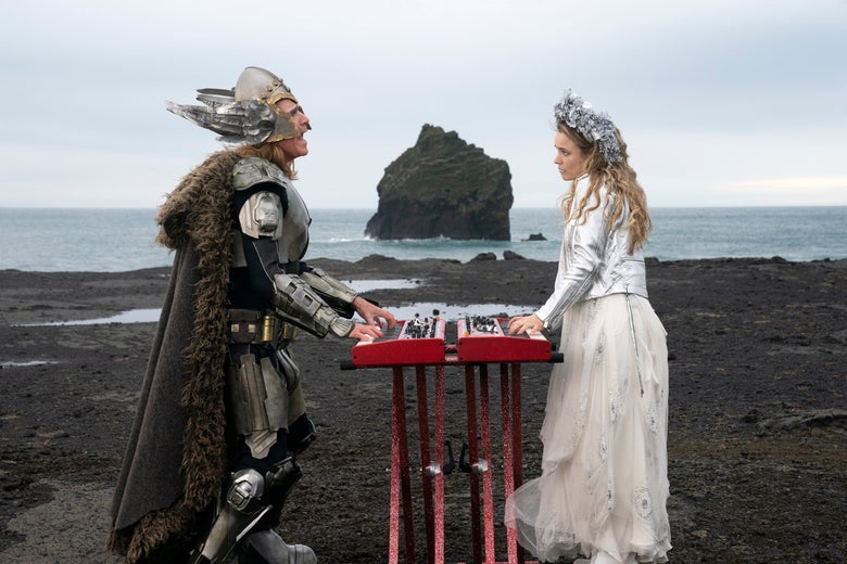 Will Ferrell, in Viking helmet, and Rachel McAdams, in jeweled tiara, play keyboards on the rocks by the ocean.