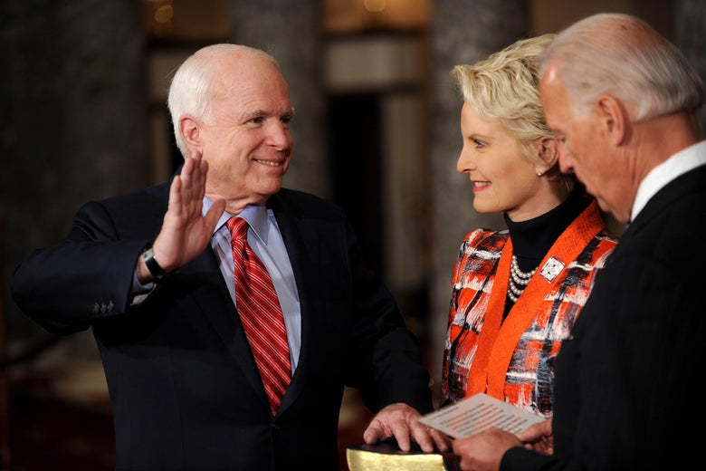 Cindy McCain holds a Bible on which John places his left hand as he raises his right hand. Joe Biden, in the foreground, reads from a piece of paper.