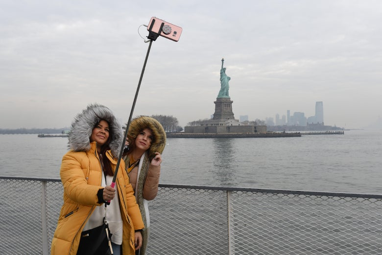 Tourists take smartphone photos after the re-opening of the Statue of Liberty in New York.