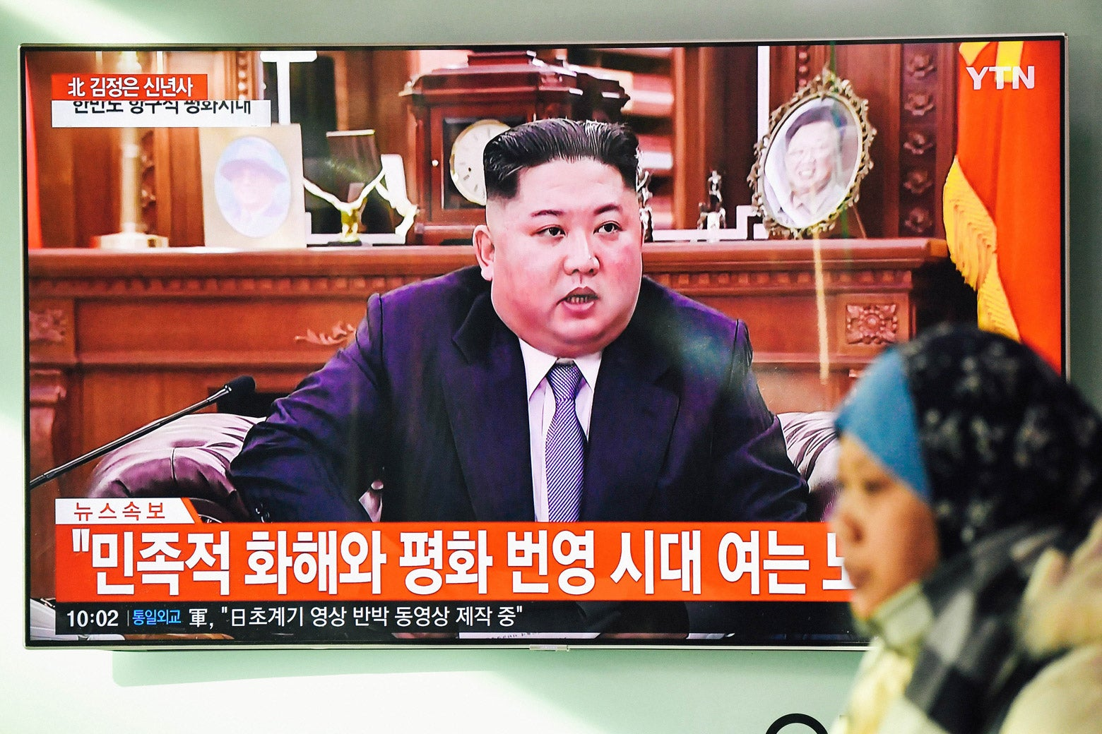 A woman walks past a television screen showing North Korean leader Kim Jong-un giving a New Year's speech.