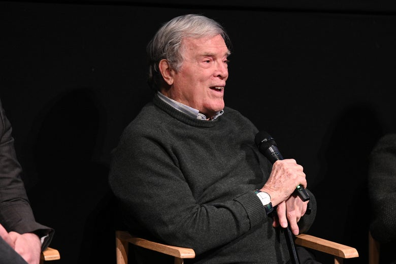 D.A. Pennebaker, sitting in a director's chair onstage, laughs during a Q&A.