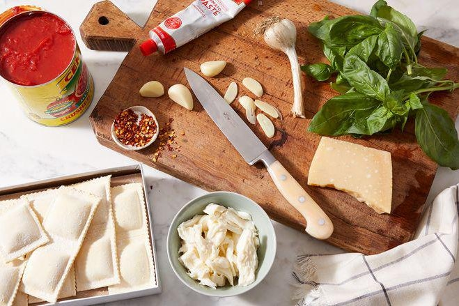 A cutting board with a knife, fresh basil, garlic cloves, and cheese. Nearby, frozen ravioli, shredded mozzarella, and an open can of tomato sauce.