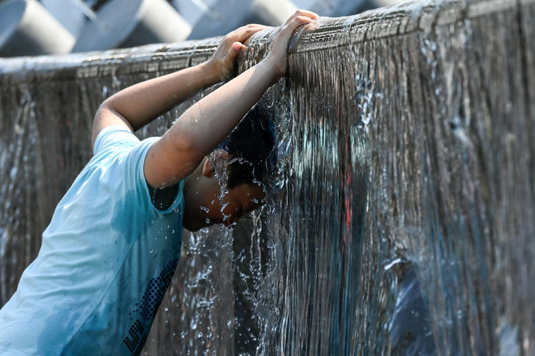 A boy in a blue T-shirt sticks his head under the water pouring off a fountain to cool off.