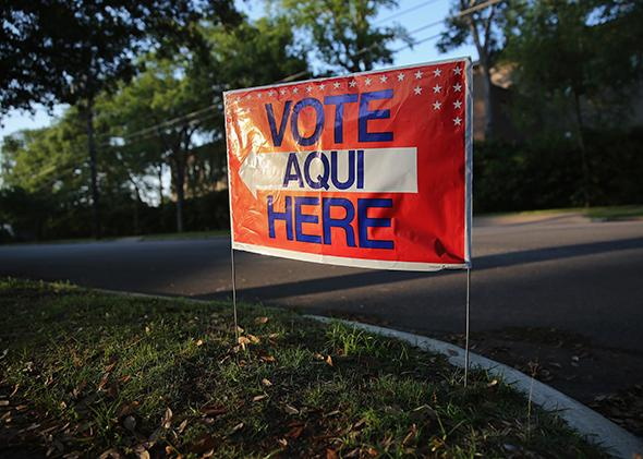 A bilingual sign draws voters to a polling center at a public library ahead of local elections on April 28, 2013, in Austin, Texas.