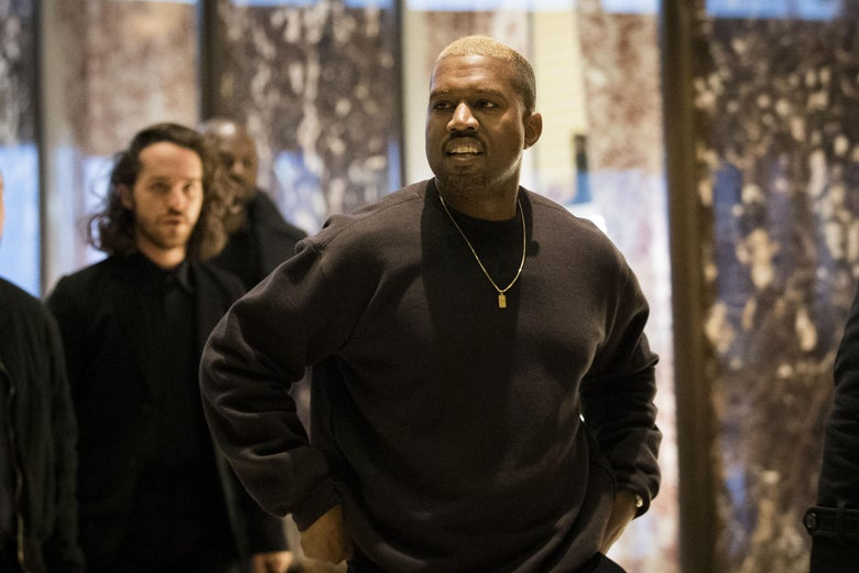 Kenya West walks and speaks wearing a black pull over and a gold chain