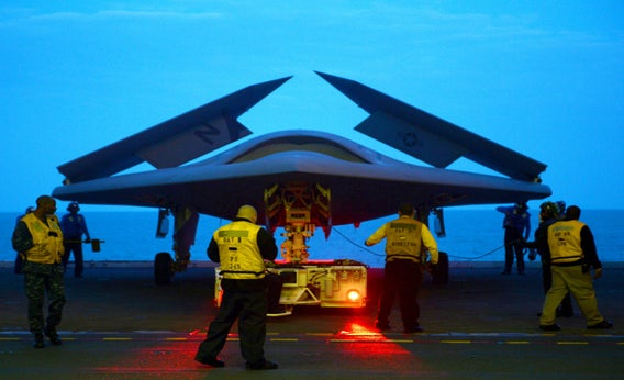 An X-47B Unmanned Combat Air System (UCAS) demonstrator is towed into the hangar bay of the aircraft carrier USS George H.W. Bush (CVN 77) May 13, 2013, in the Atlantic Ocean.