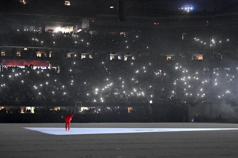 A man in red stands on an empty football field bathed in gray and white light. There are bright lights in the stands, held by audience members.