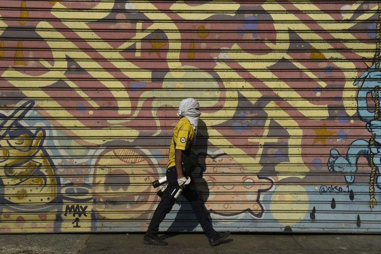 An opposition demonstrator walks by a graffiti.