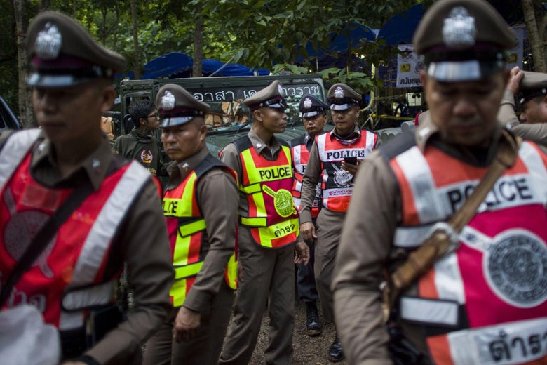 Policemen stand guard outside the cave where the kids are trapped