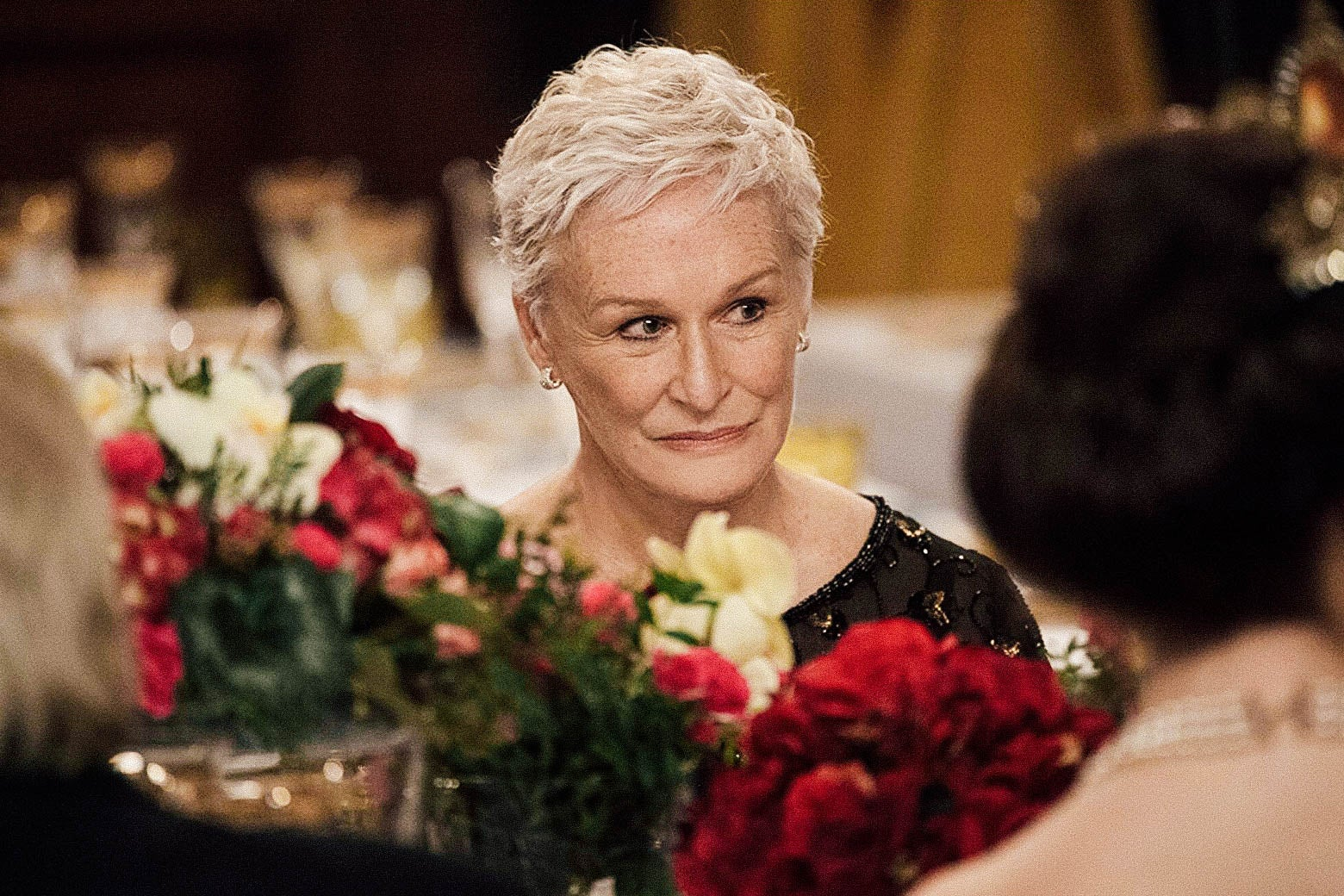 Glenn Close at a banquet table seen behind a flower centerpiece.