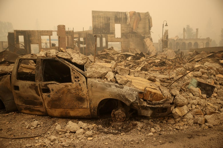 A burned truck is seen next to a pile of charred rubble and a damaged building.