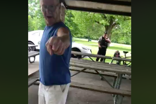 A man points a finger at the camera while a police officer looks on in the background