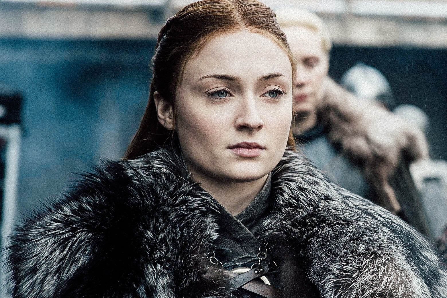 Sophie Turner as Sansa Stark stands while wearing a fur coat in this still from Game of Thrones.