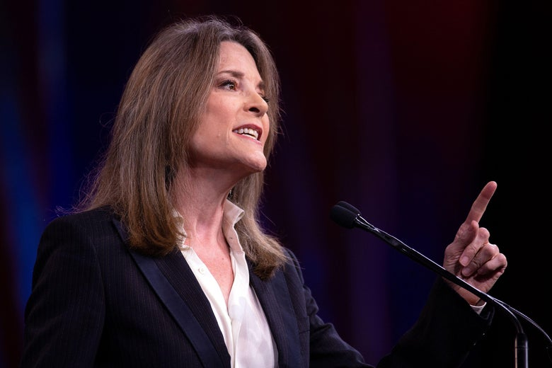Marianne Williamson points a finger while speaking at a podium.