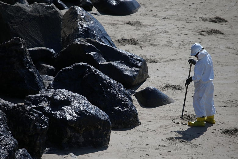 A worker in hazmat gear rakes sand next to oil-covered rocks on a beach.