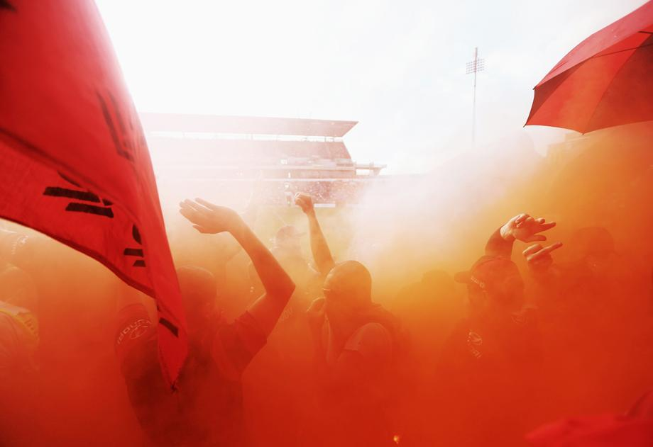 Western Sydney Wanderers fans cheer as a flare is lit during the round 27 A-League match between the Newcastle Jets and Western Sydney at Hunter Stadium on March 29, 2013, in Newcastle, Australia.