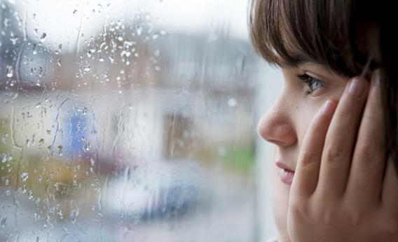 Young child looking out of window on rainy day.