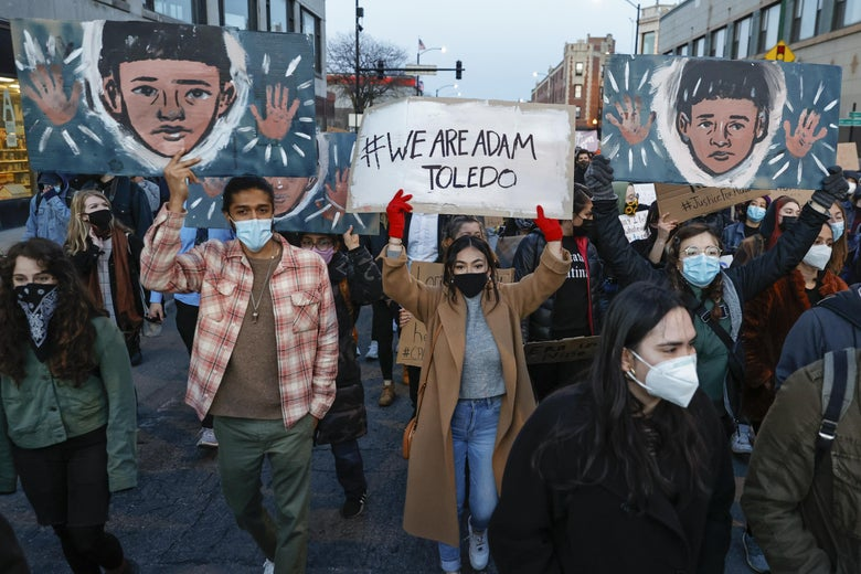 """Protesters hold up signs with drawings of Adam Toledo and text like, """"We Are Adam Toledo."""""""