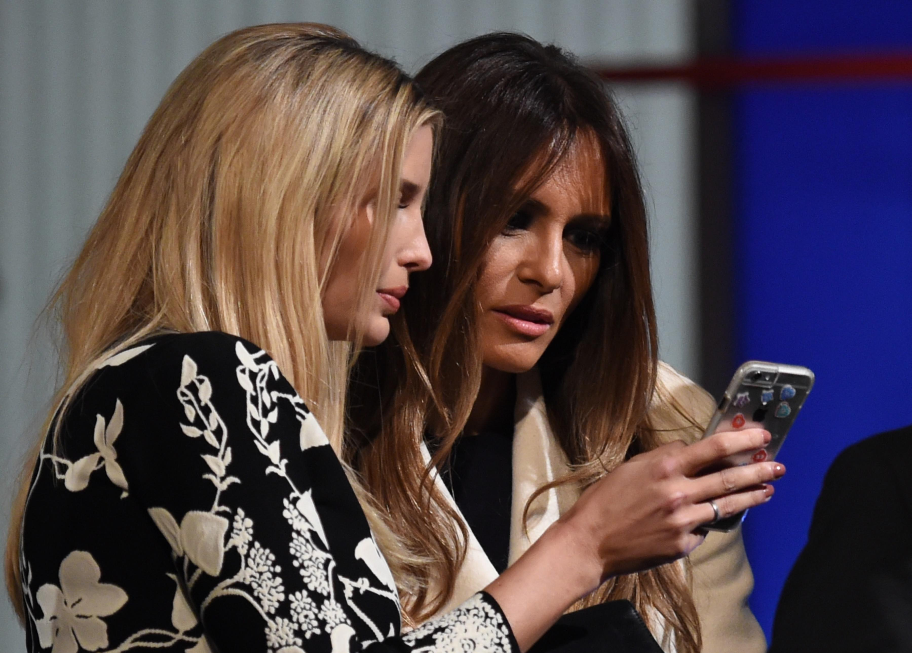 Ivanka and Melania Trump look at a smart phone after the Republican Presidential debate in Charleston, South Carolina on Jan. 14, 2016.