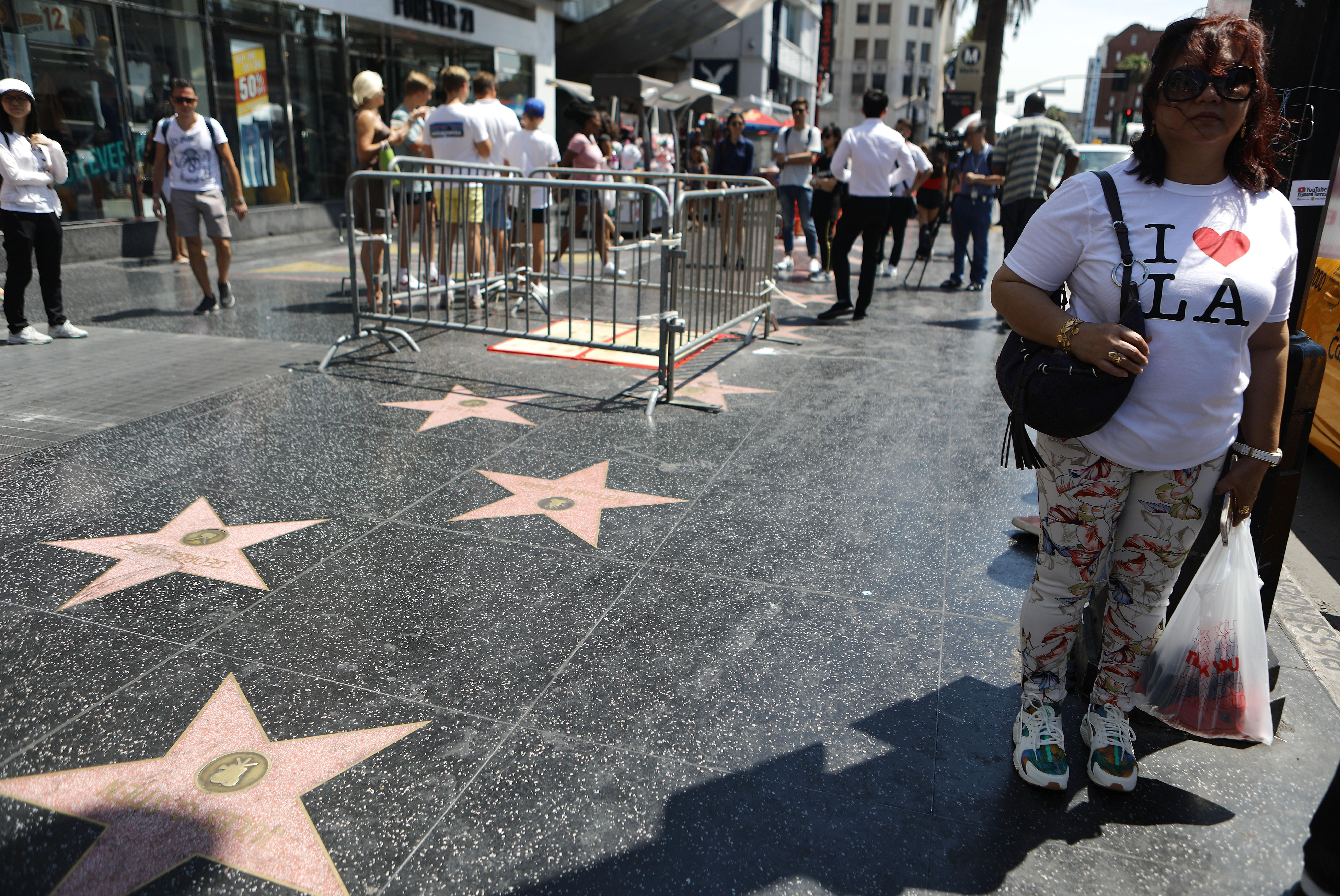 A woman wearing an I Heart LA shirt stands near a barricade surrounding the location of the vandalized Hollywood star of President Donald Trump.