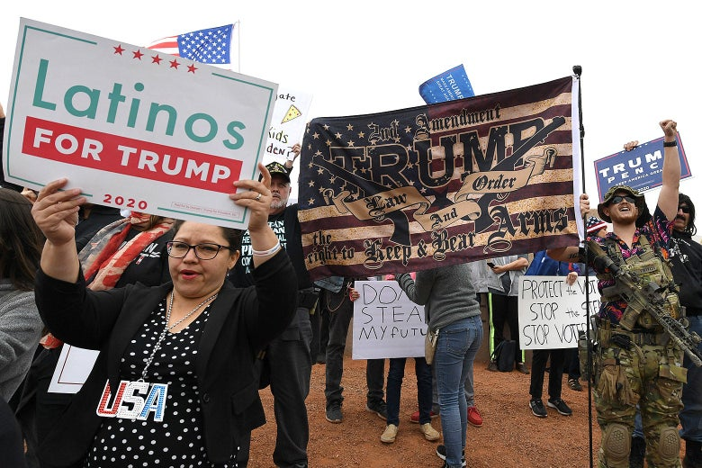 "Trump supporters hold signs reading ""Latinos for Trump"" and ""Trump Pence"" along with a Trump-branded flag."