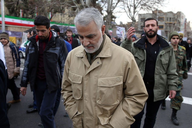 Qassem Soleimani, wearing civilian clothes, walks during a street procession with his eyes down.