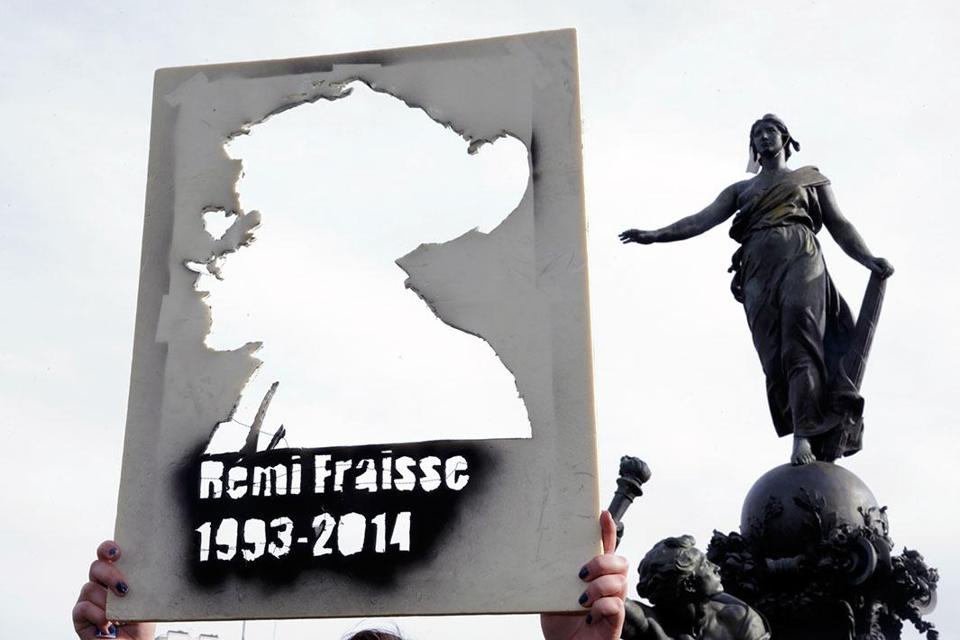 "A student holds a cutout portrait of Remi Fraisse during a demonstration at the Place de la Nation in Paris on Nov. 13, 2014, against ""police brutality"" and in memory of the 21-year-old environmentalist who died during a violent standoff last month between police and ecology protesters seeking to prevent construction of a dam in Sivens"