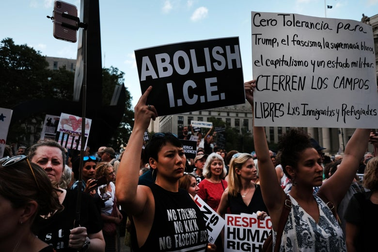 "Protesters hold up signs during the daytime. The sign in the middle reads, ""ABOLISH I.C.E."" A woman holds up a sign in Spanish to the right."