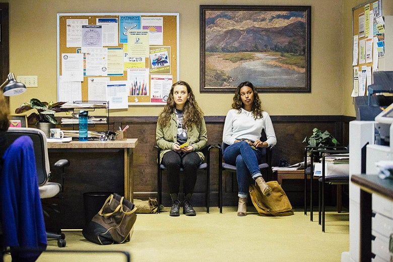 Alisha Boe and Katherine Langford sit in chairs against a wall in 13 Reasons Why