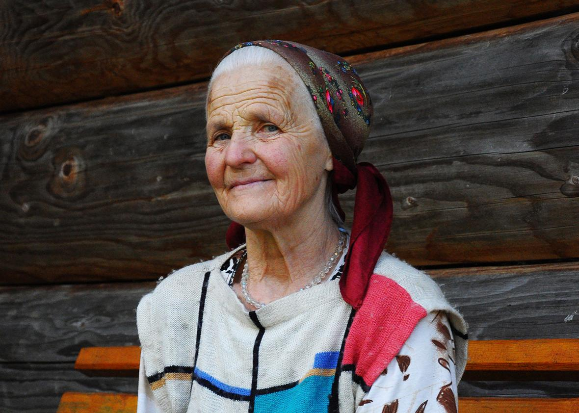 Pani Maria, 73, the matriarch of the Illyuk family, outside her cottage above the village of Dzembronya in the Carpathian Mountains.