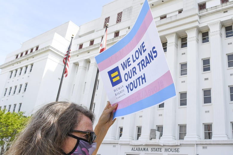 "A woman holds a sign that reads ""We love our trans youth"" outside the Alabama state house."