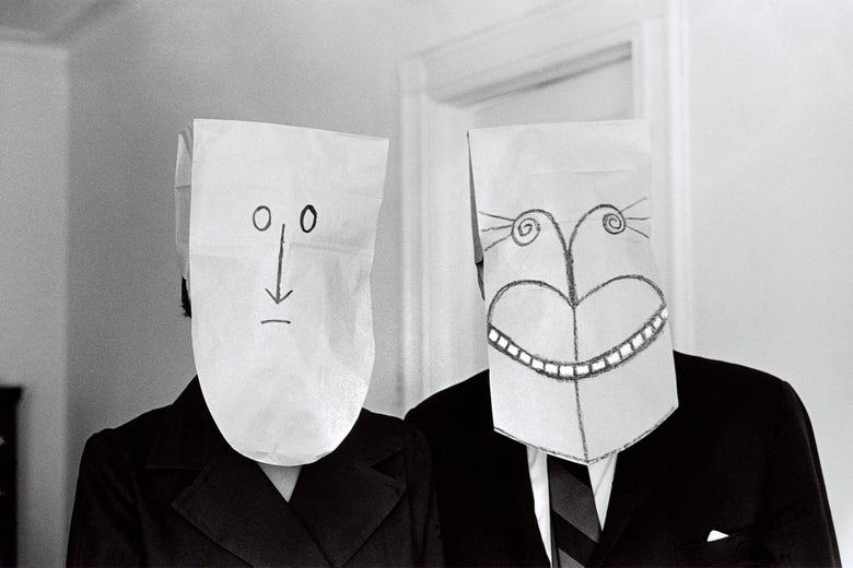 Two people wearing masks, one smiling, one frowning.