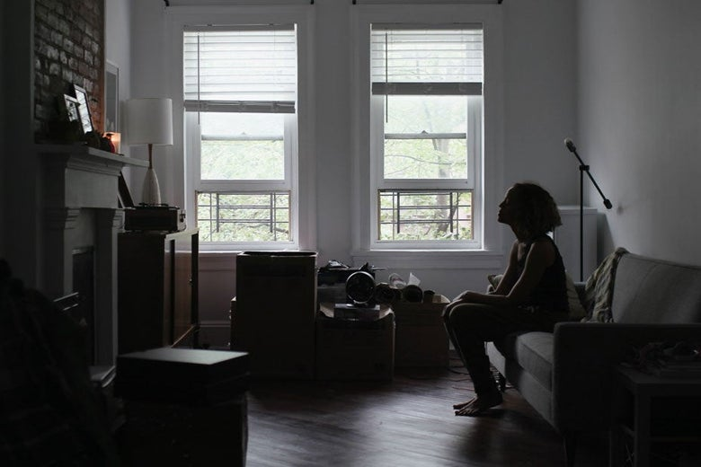 A woman sits alone in an apartment with music equipment