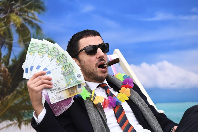 An Oxfam activist stages a satirical street-play mimicking a wealthy person hidding his money in a tax haven, on December 5, 2017 near the European institutions in Brussels, within a meeting of European Union ministers over a credible blacklist of non-EU tax havens.  The EU has struggled for over a year to finalise the blacklist, with smaller, low-tax EU nations such as Ireland, Malta and Luxembourg worried about scaring off multinationals. / AFP PHOTO / EMMANUEL DUNAND        (Photo credit should read EMMANUEL DUNAND/AFP via Getty Images)