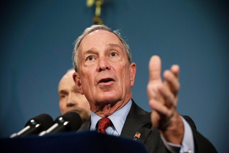 Michael Bloomberg speaks into a microphone and raises his hand.