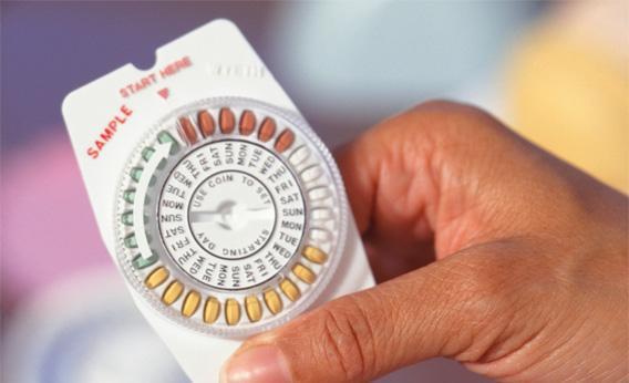 Woman holding birth control pills.