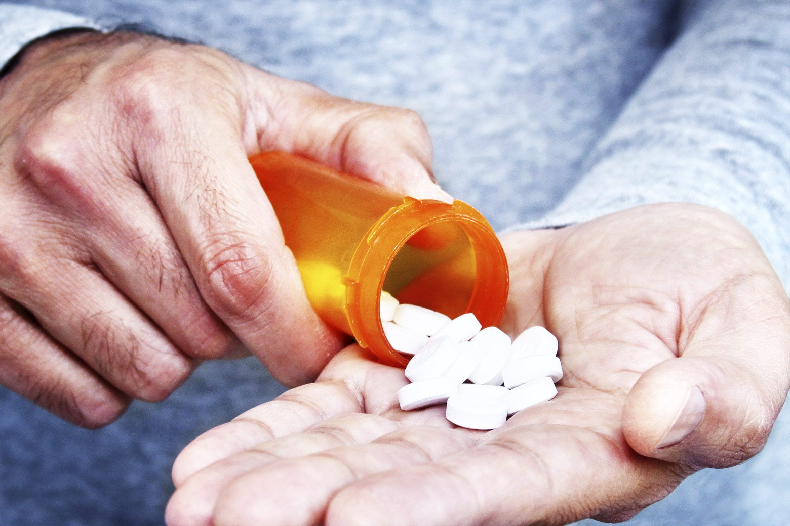 A man pours pills from a bottle into his hand.