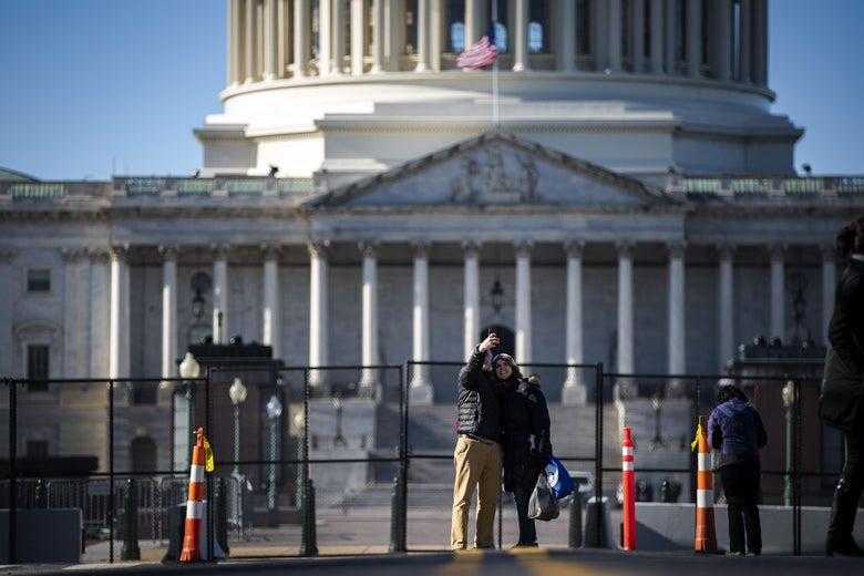 A smiling couple takes a selfie in front of the new security fence outside the Capitol dome
