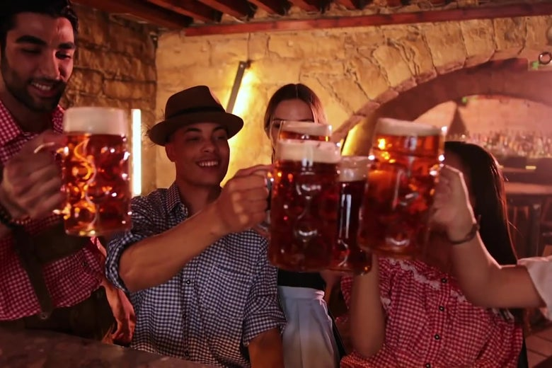 A stock shot of people in German clothing clinking beer steins at an Oktoberfest celebration.