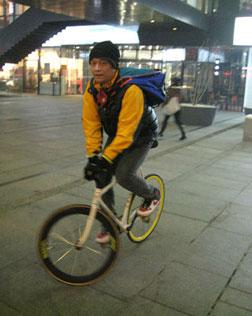 Nie Zheng performs a track stand on his fixed-gear bike in a high-end shopping plaza in Beijing's Central Business District