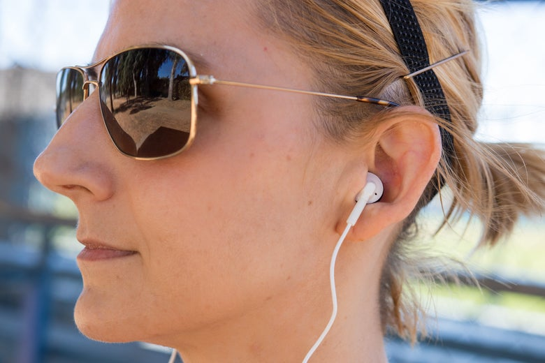 A woman wearing InTone Wireless earbuds.