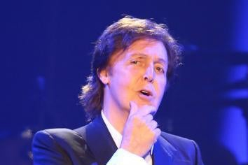 Paul McCartney onstage with a hand on his chin as if in contemplation.