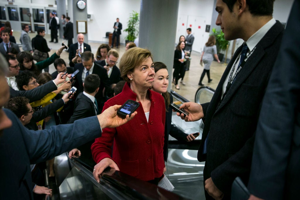 Tammy Baldwin surrounded by reporters on an escalator in the Capitol.