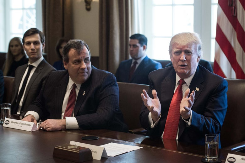 Jared Kushner, Chris Christie, and Donald Trump are all seated at a table in the White House. Kushner looks ahead, while Christie, sitting at the center of the table, looks at Trump, who is speaking.