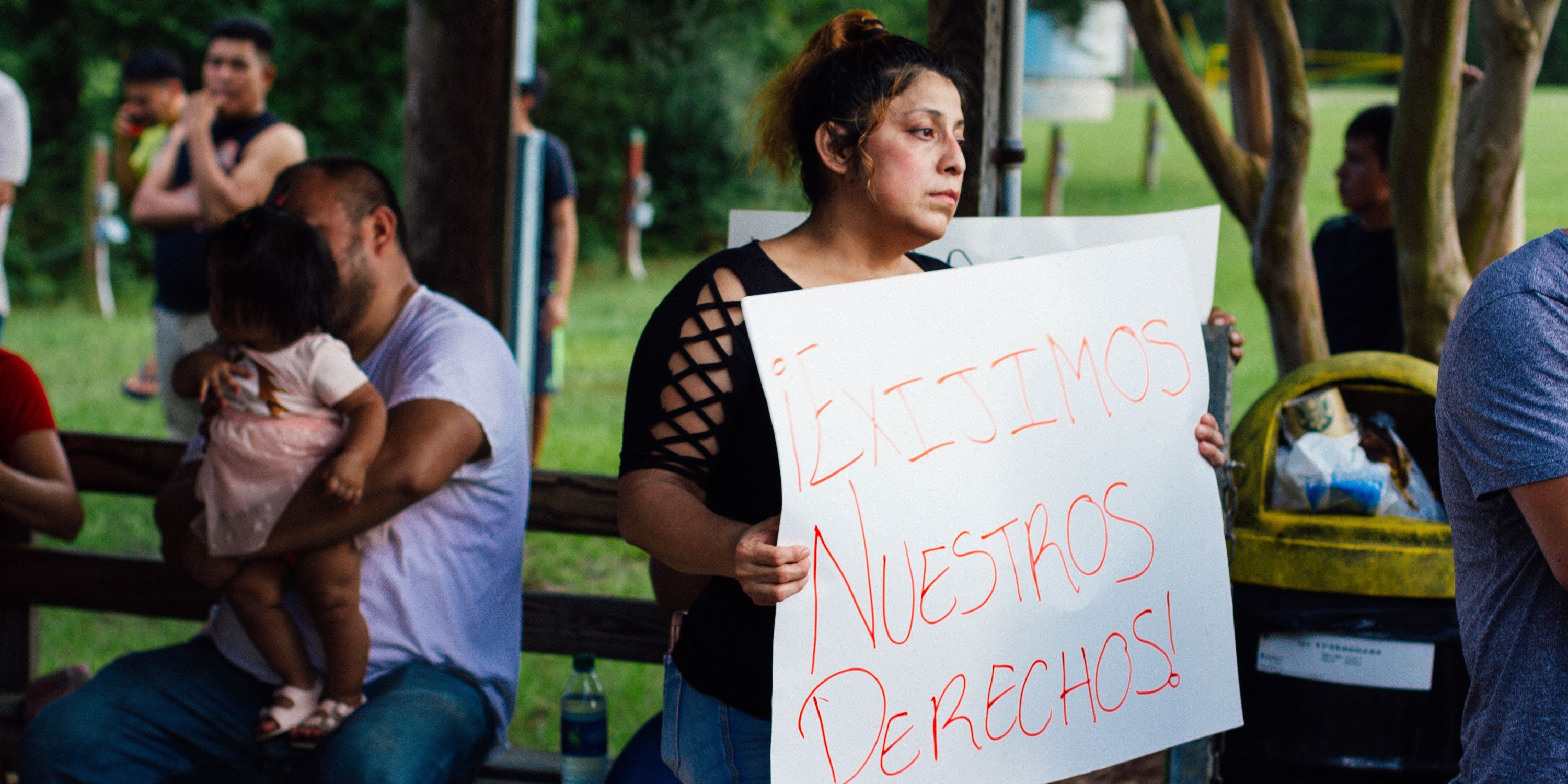 "Workers protest in a park. One woman holds a sign that reads ""EXIJIMOS NUESTROS DERECHOS,"" or ""WE DEMAND OUR RIGHTS."""