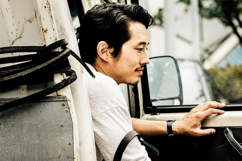 Steven Yeun in a car.